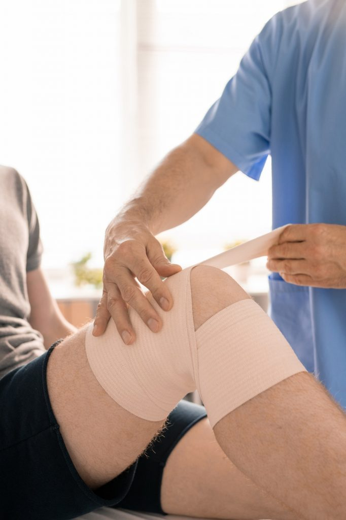 Hands of clinician in blue uniform wrapping injured knee of young patient